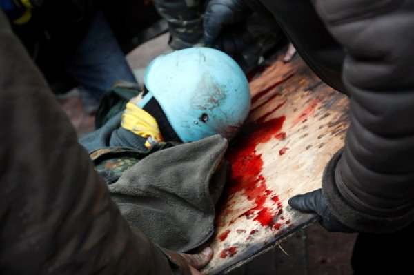 Anti-government protesters carry an injured man on a stretcher after violence erupted in the Independence Square in Kiev