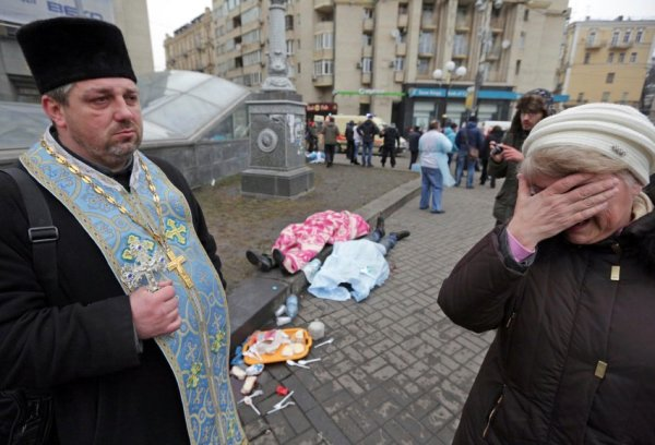 An Orthodox priest holds a cross as a woman reacts next to dead bodies following violence in Independence Square in Kiev