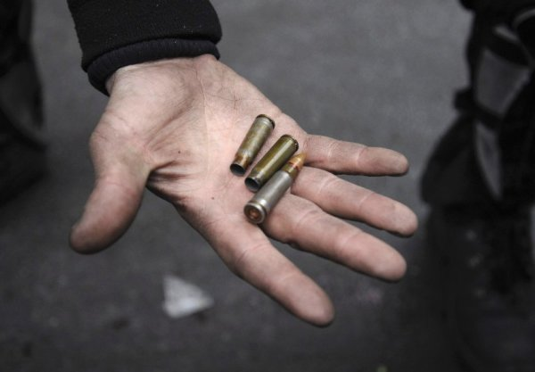 A man shows a bullet and empty casings during clashes with riot police near Independence Square in Kiev