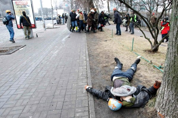A dead body is seen on the ground after violence erupted in the Independence Square in Kiev