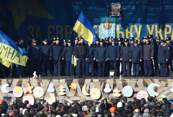 Police officers from Lviv who have arrived to join anti-government protesters appear on a stage in Independence Square in Kiev