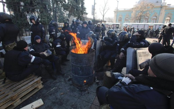 Riot police warm themselves near the Ukrainian parliament in Kiev
