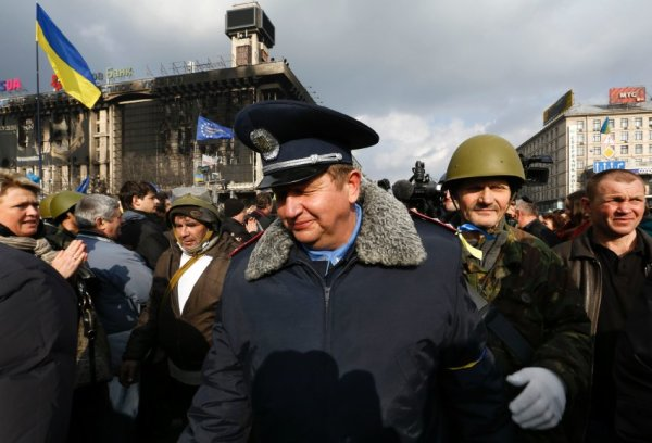 A police officer who has joined anti-government protesters gets emotional as he is escorted during a rally in Independence Square in Kiev